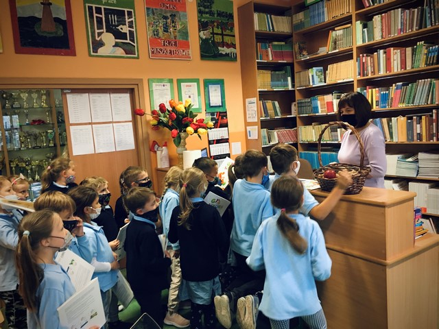 Dzieci z klasy 1 stoją przed kontuarem w bibliotece, oczekując na zwrot książek