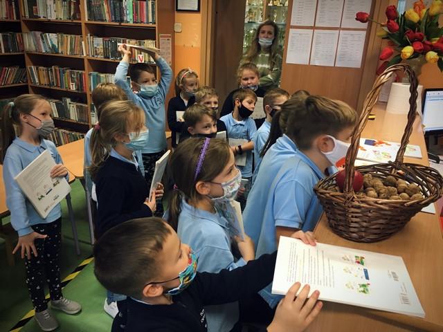 dzieci w bibliotece oddają podręczniki