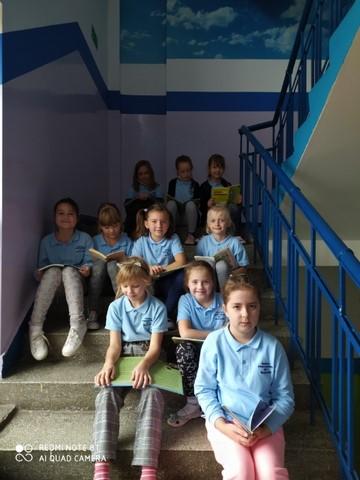 10 dziewczynek siedzi na schodach i czyta książki