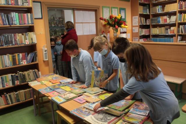 Czworo dzieci w bibliotece wybiera książki do wypożyczenia