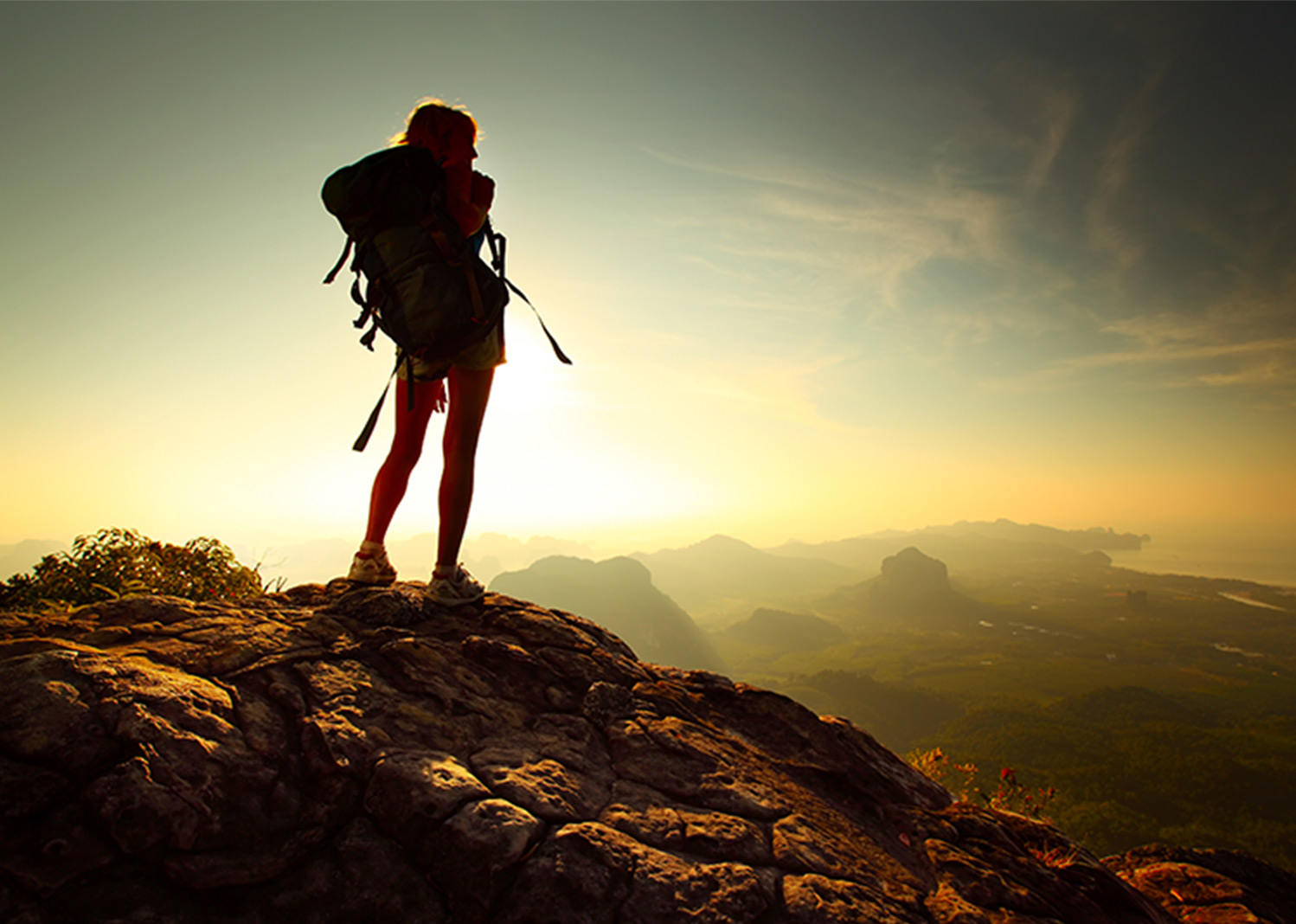 Marriott promo of a woman standing the edge of a cliff over looking the mountains.