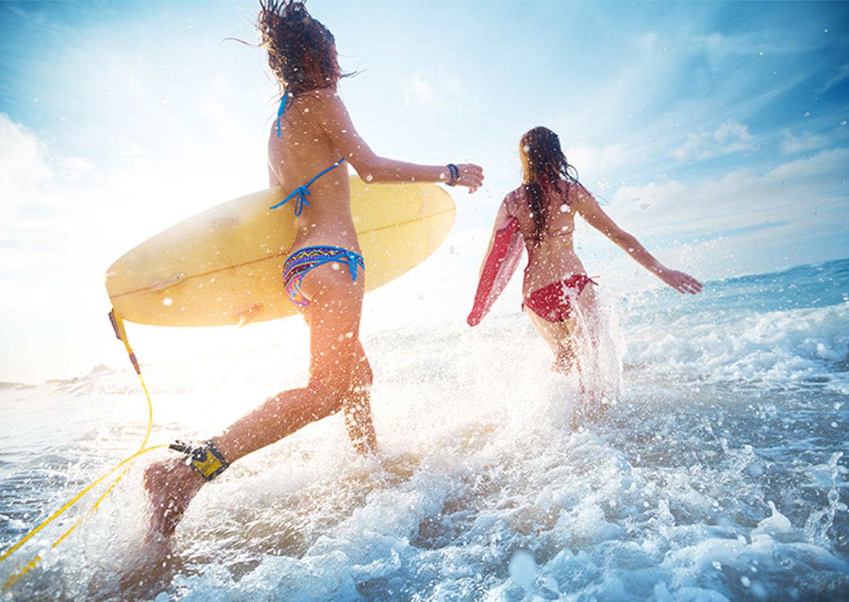Hyatt Promo two girls going surfing on the ocean