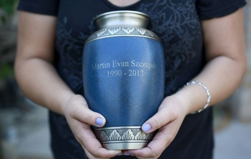 Inez Szczupak holds an urn filled with the ashes of her son Martin, who died of a drug overdose, outside her home in the Staten Island borough of New York August 19, 2015.