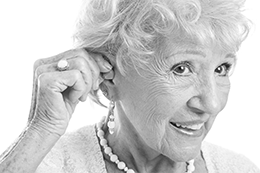 Elderly Woman Adjusting Her Hearing Aid