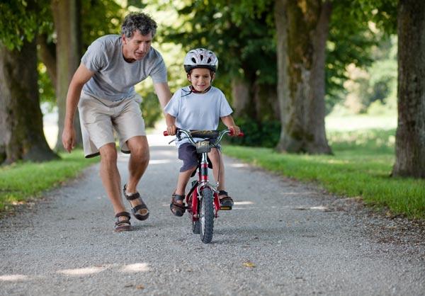Pappa lærer gutt å sykle