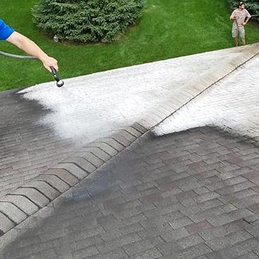 Pressure washing a roof using soft washing process