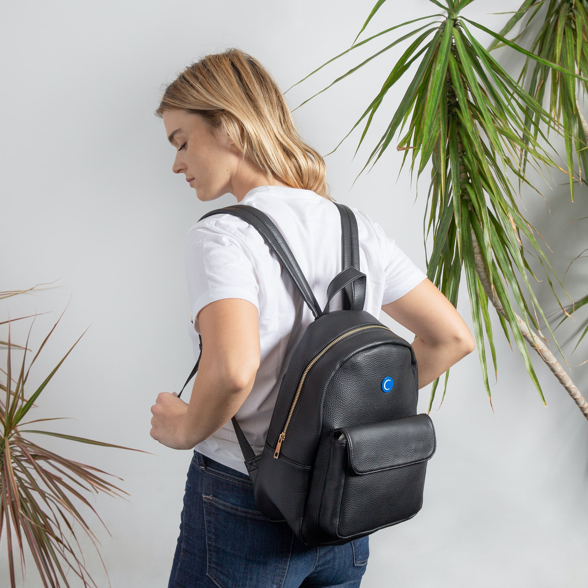 Photo of a woman putting on a backpack