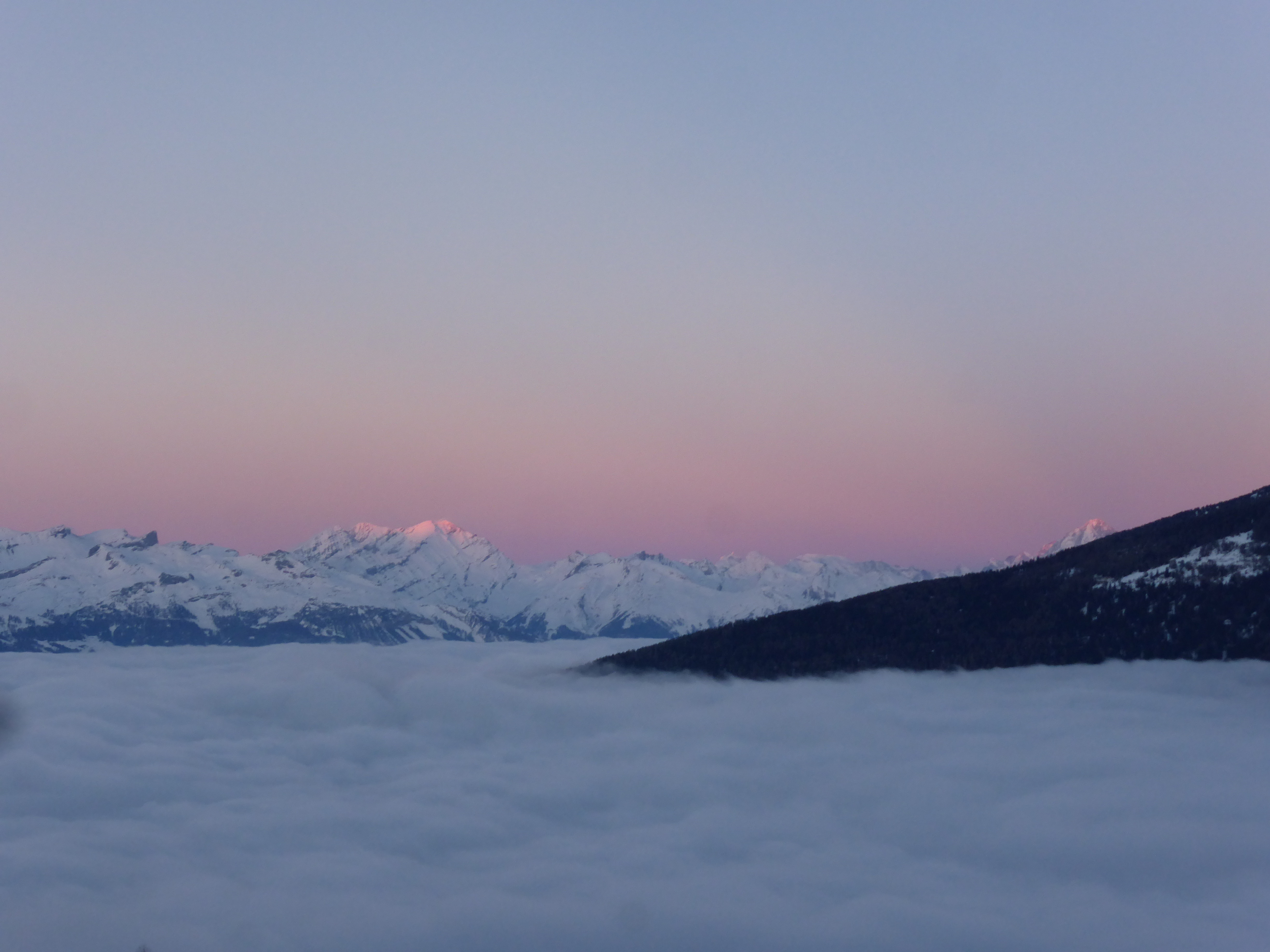 Photo of winter sunset above the clouds.