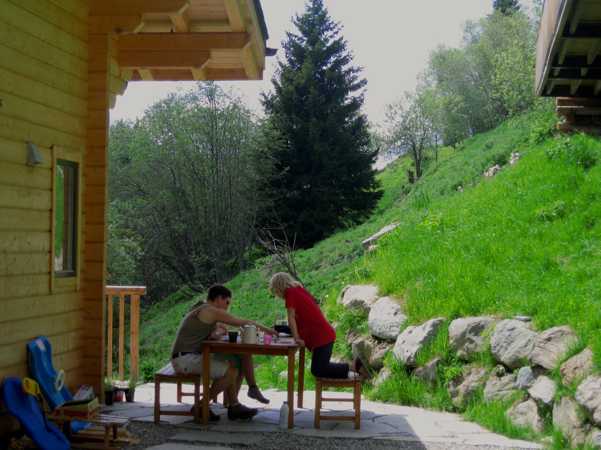 photo of family playing board game in the shadow of the chalet