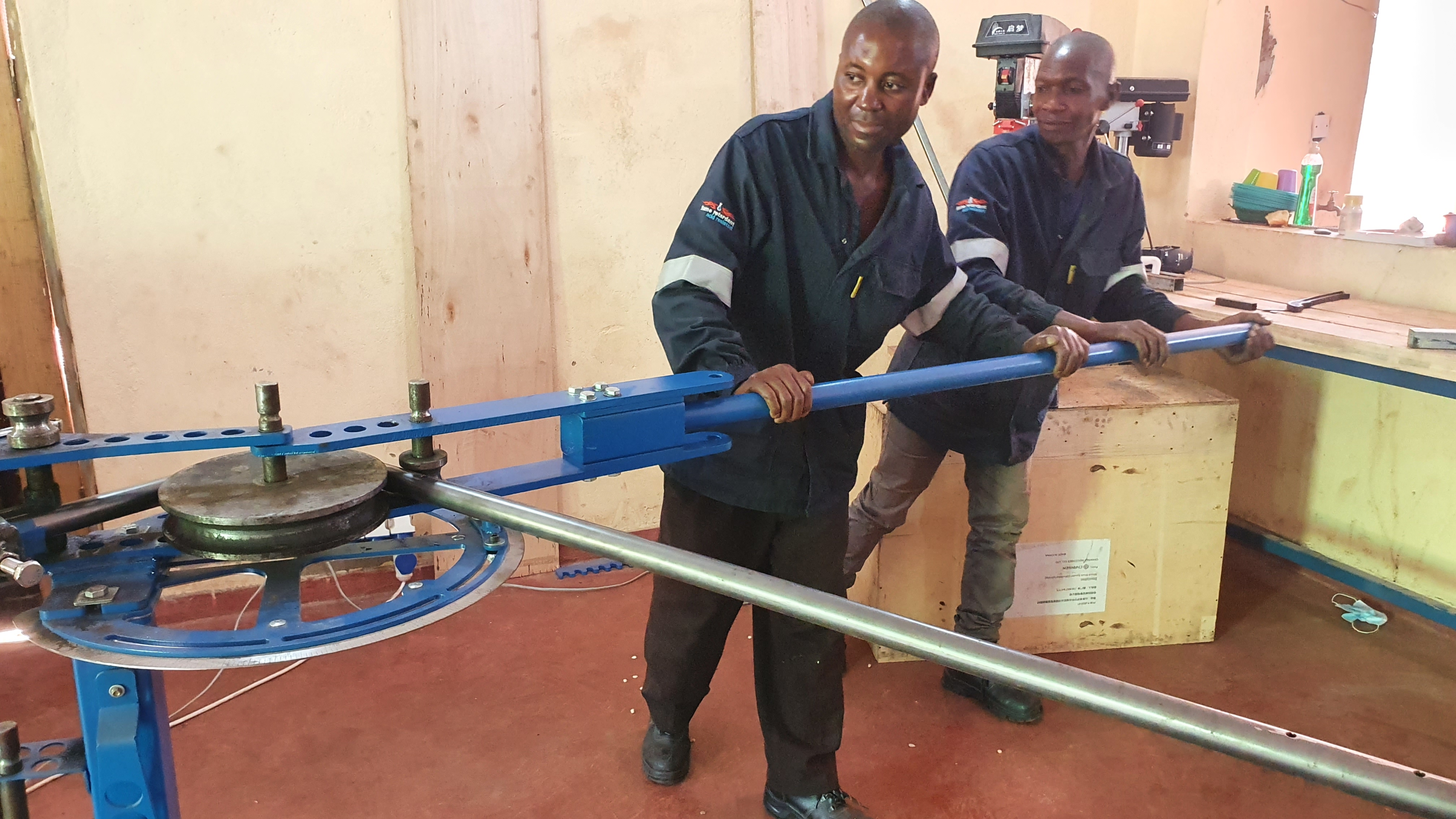 Mr. Bright Chome and Jimmy, working on the steel tube bending machine.