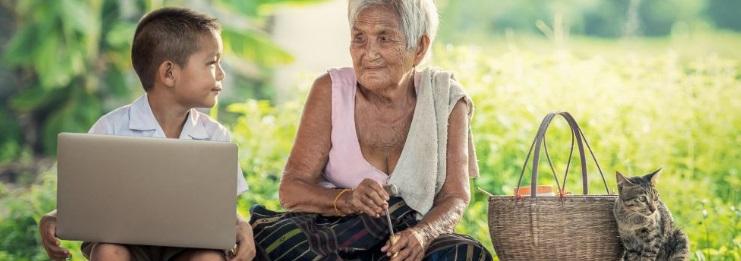 Menino com notebook olhando para senhora fazendo artesanato em um campo com bolsa de palha e gatinho ao lado