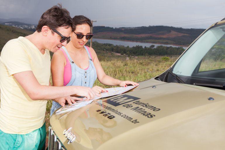 casal olhando um mapa no capô do jeep escrito turismo de Minas