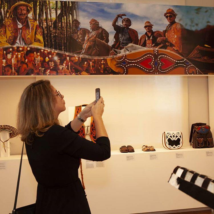 Festival Artesol, mulher fotografa sala com objetos feitos de couro por mestres artesãos brasileiros