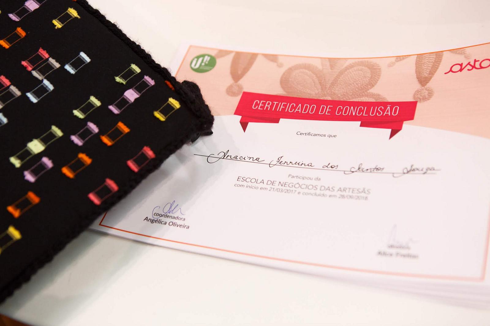 Certificado de conclusão de curso da Escola de Negócio das Artesãs da Rede Asta em parceria com a IF! com capelo ao lado