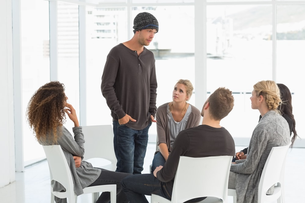 Man with hat talks to support group members