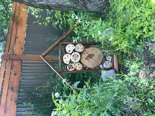Mason bee house made with holes drilled into logs protected under a wood roof, against a fence