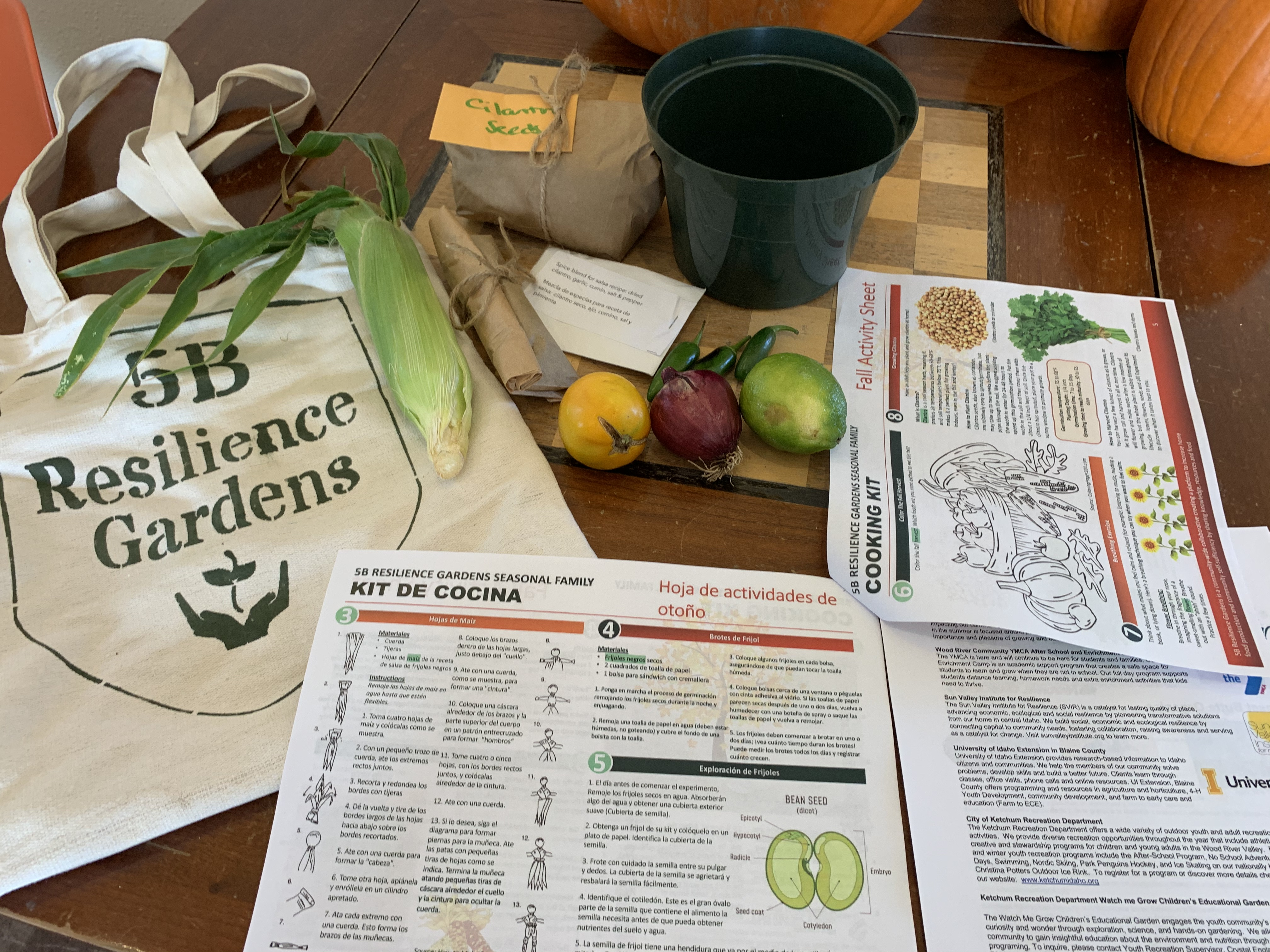 Full SPROUT kit offering with canvas bag, local produce, soil, pot, and activity packet in Spanish and English