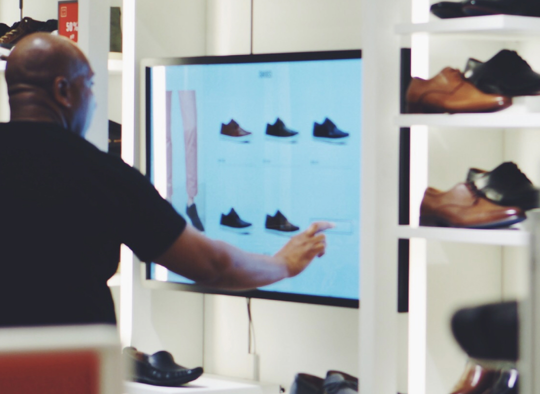 A man interacts with a large screen digital interface in a shoe store