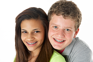 two kids smiling with braces showing off their orthodontic work
