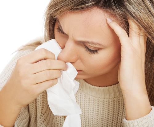 woman suffering from non-allergic rhinitis holding a white tissue to her runny nose