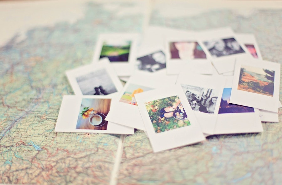 photos in a pile over a map