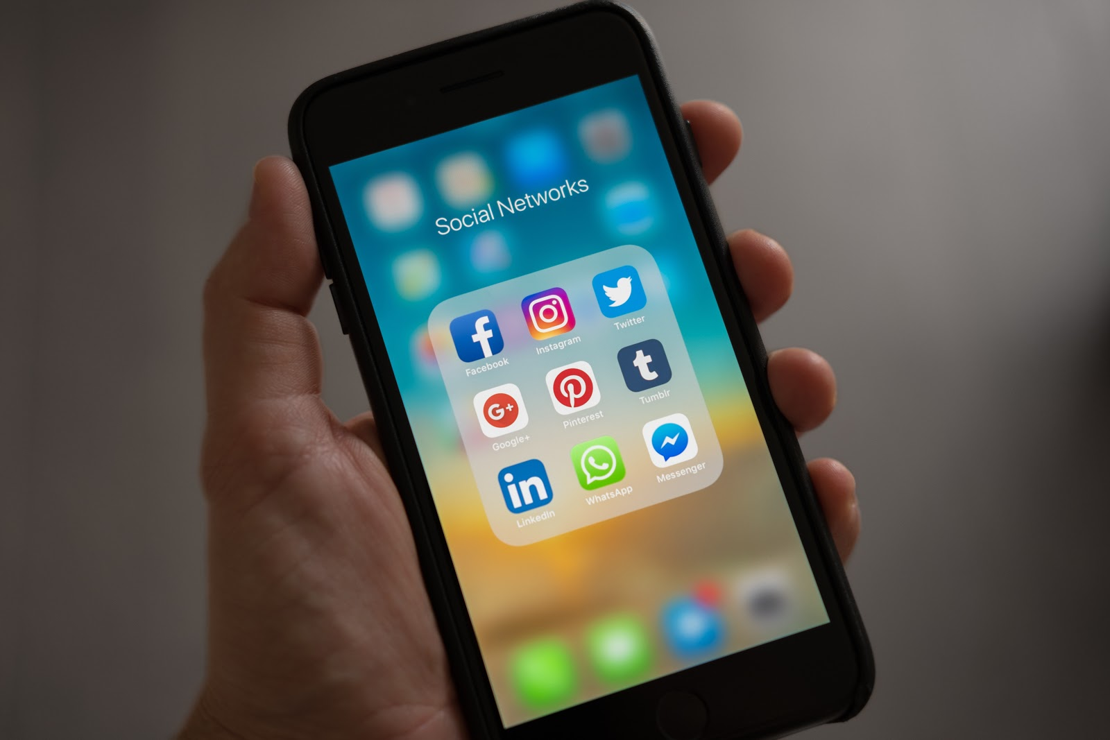 hand holding phone with social network apps