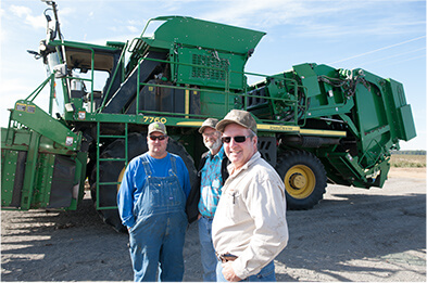 Farmers in front of baling tractor