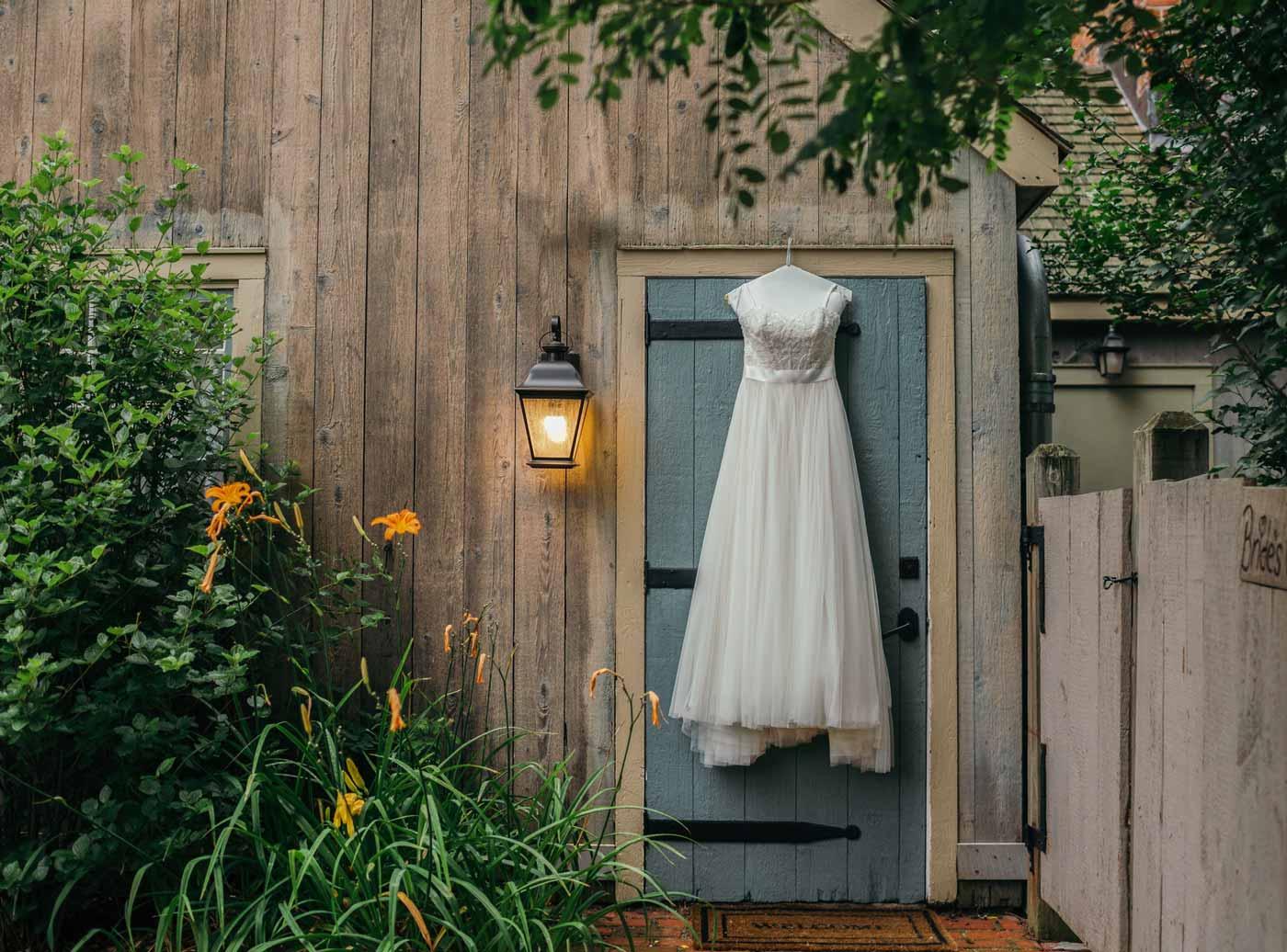 A wedding dress hanging on a rustic cabin door.
