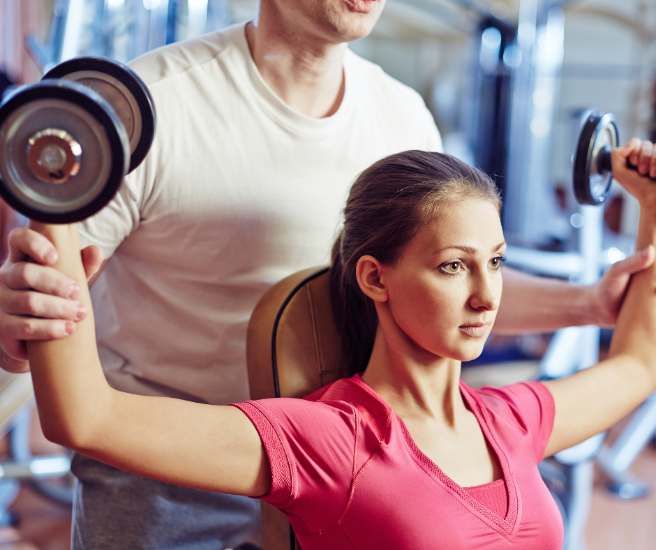 Black gold physiotherapist helping patient in lifting dumbbells
