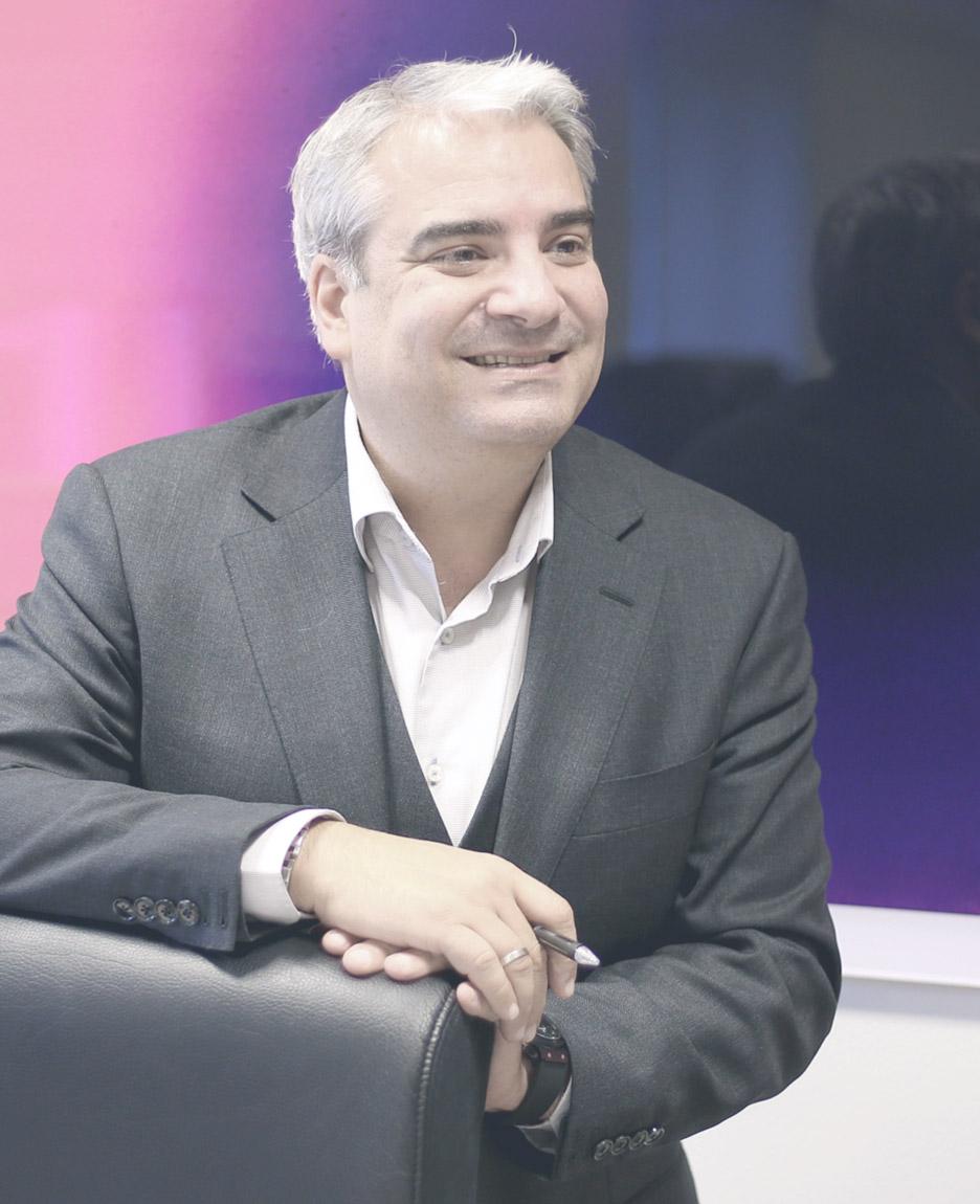Oskar Sardi smiling while standing behind an office chair