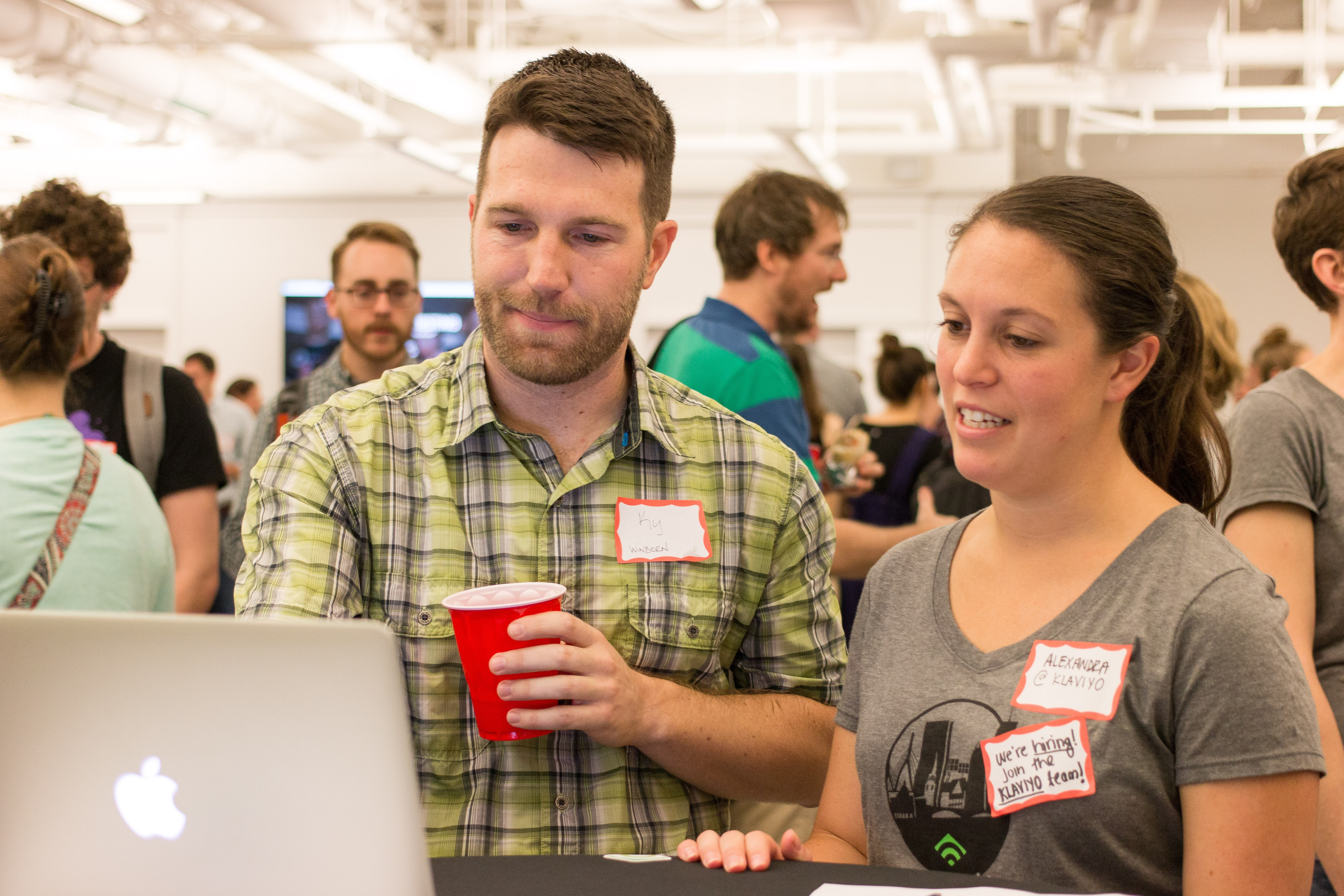 A man tests a product on a computer while a user researcher looks on