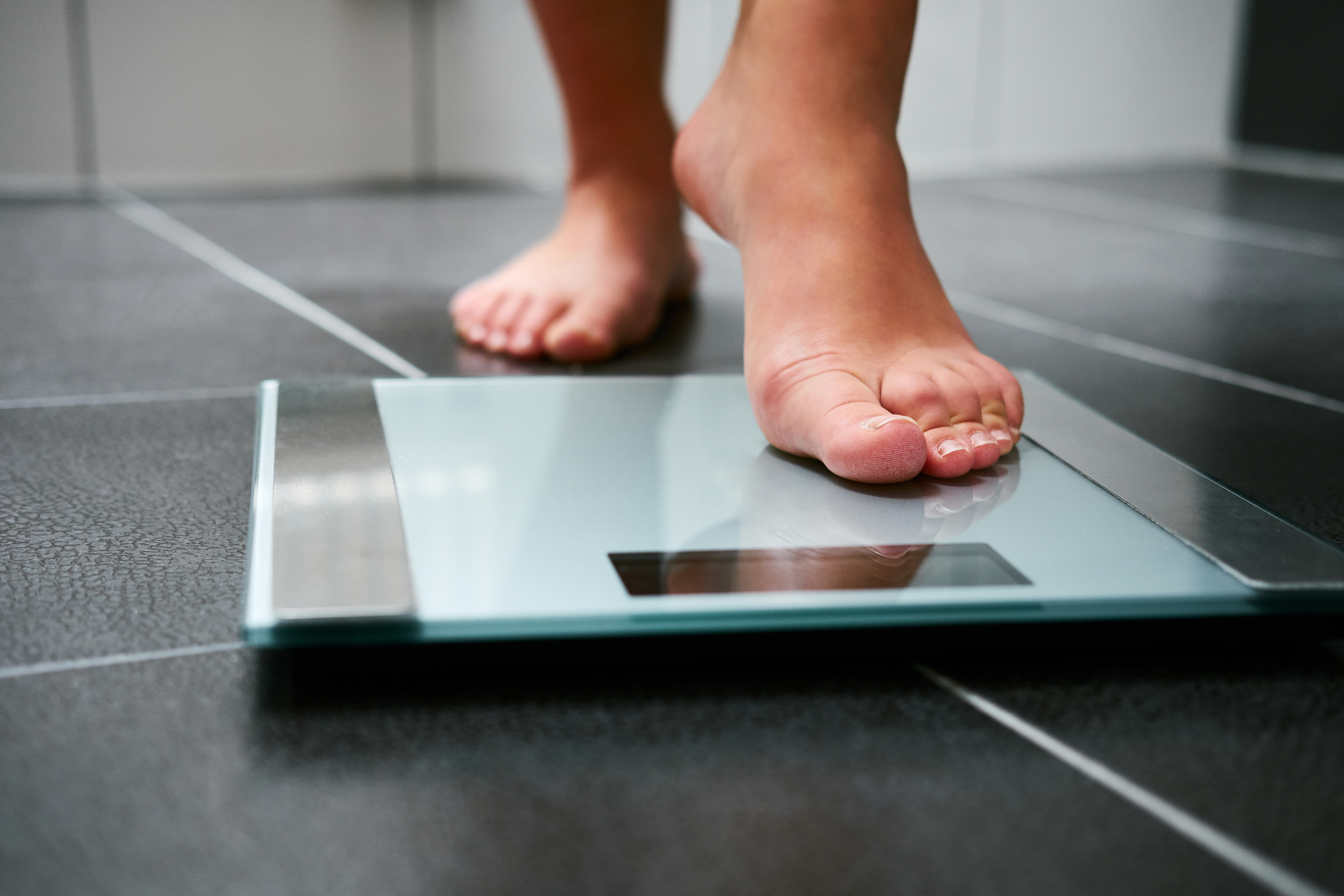 Person stepping onto weight scales BMI