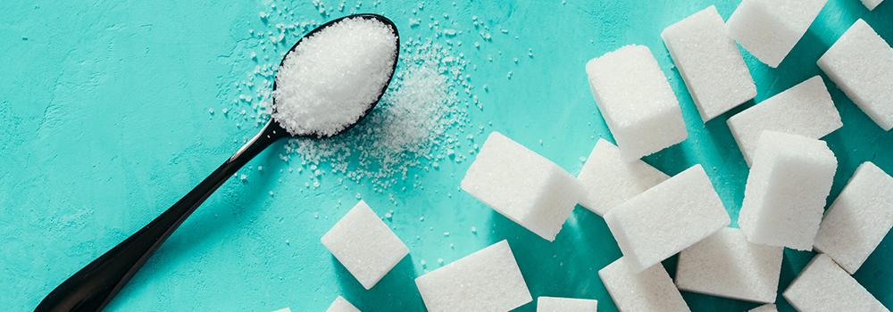 sugar cubes and sugar on a teaspoon blue background