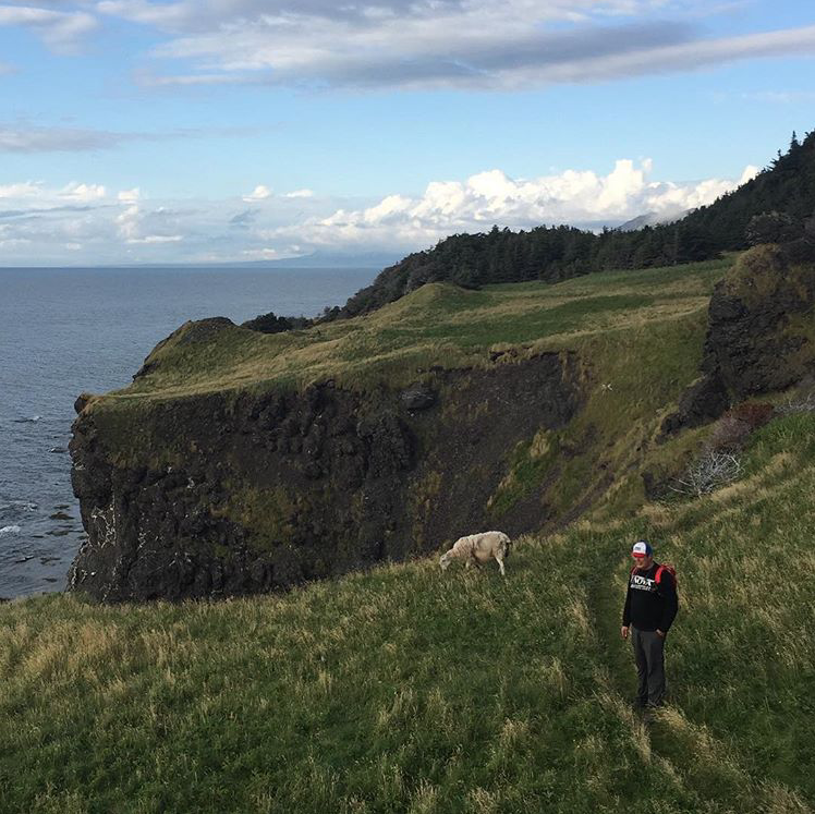 Photo of designer Peter Chilton on the shores of Newfoundland, Canada with a sheep.