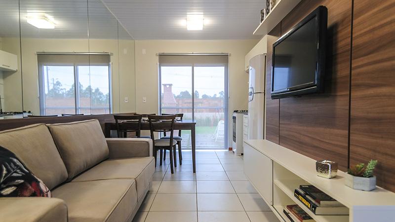 Sala e cozinhas decoradas com vista para o jardim privativo do Residencial Winter Park na Restinga