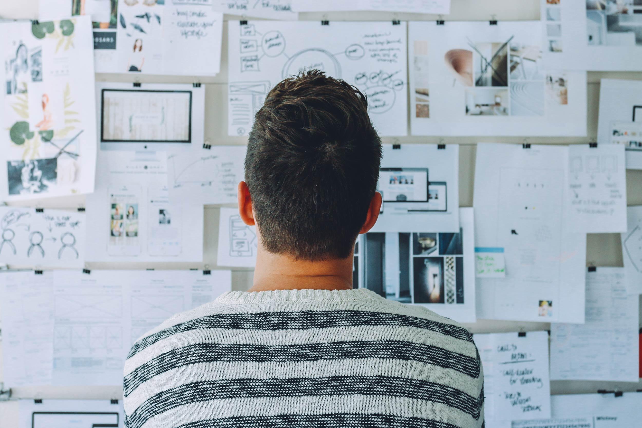 A man staring at pin ups pondering what to do next