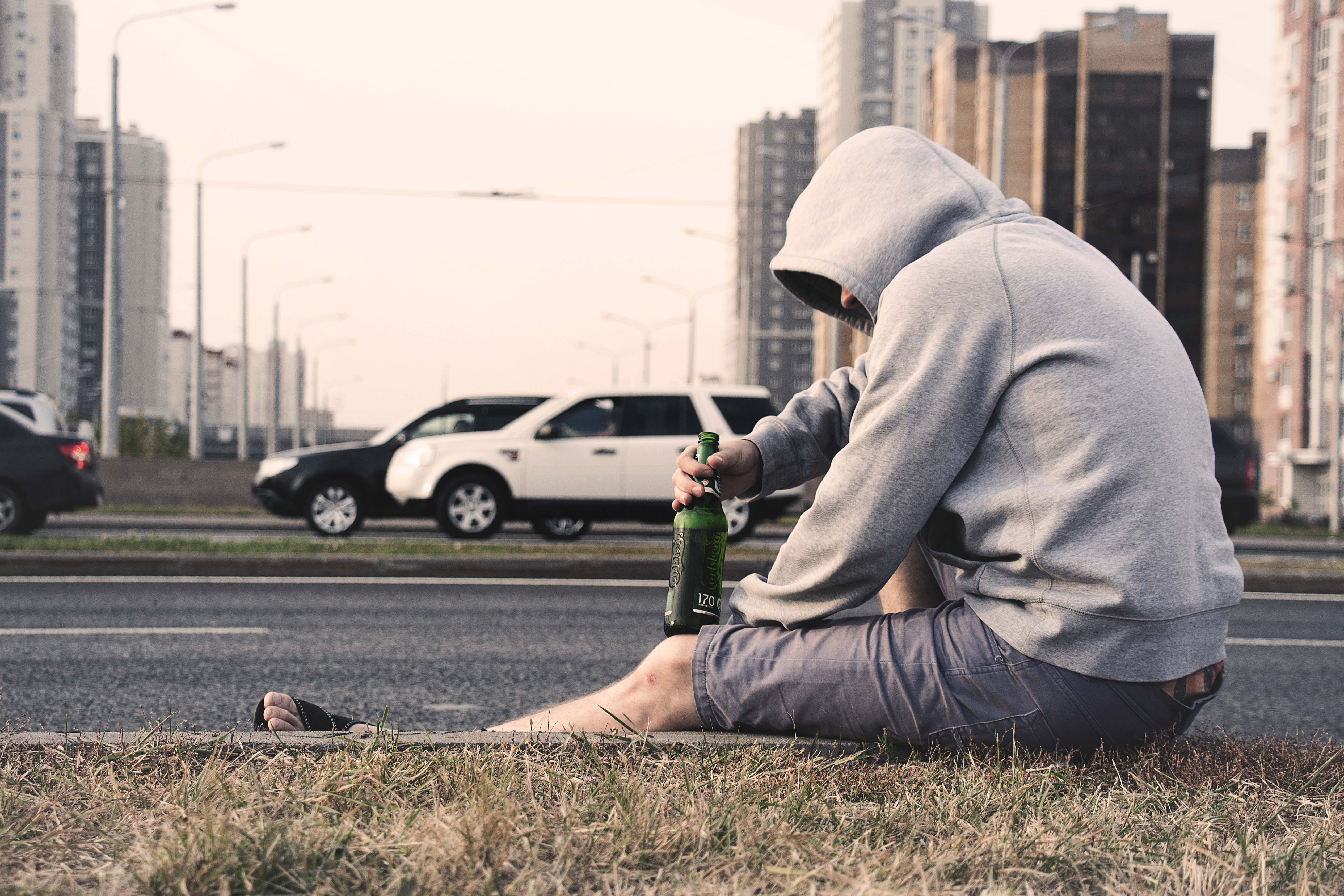hooded man sitting next to road with bottle of alcohol