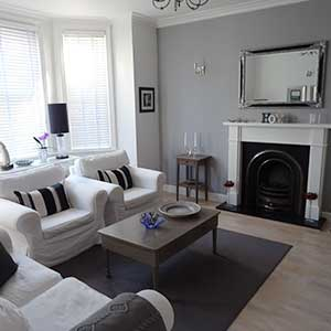 Living room with white sofas and fireplace in Bournemouth