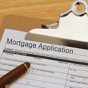 Mortgage application form on clipboard with pen