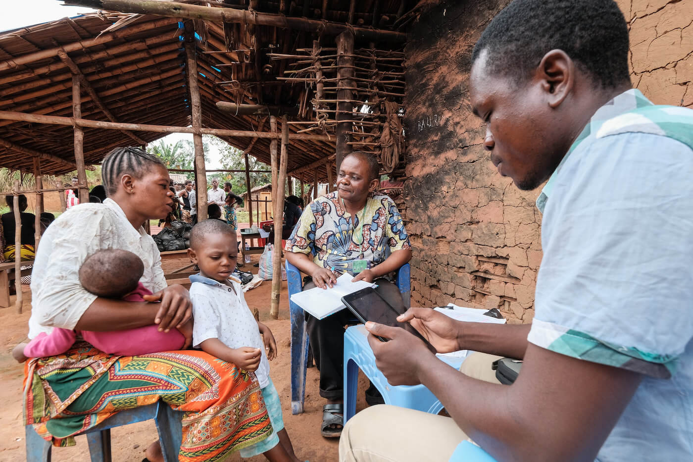 A mother and her child being interviewed by two community health workers.