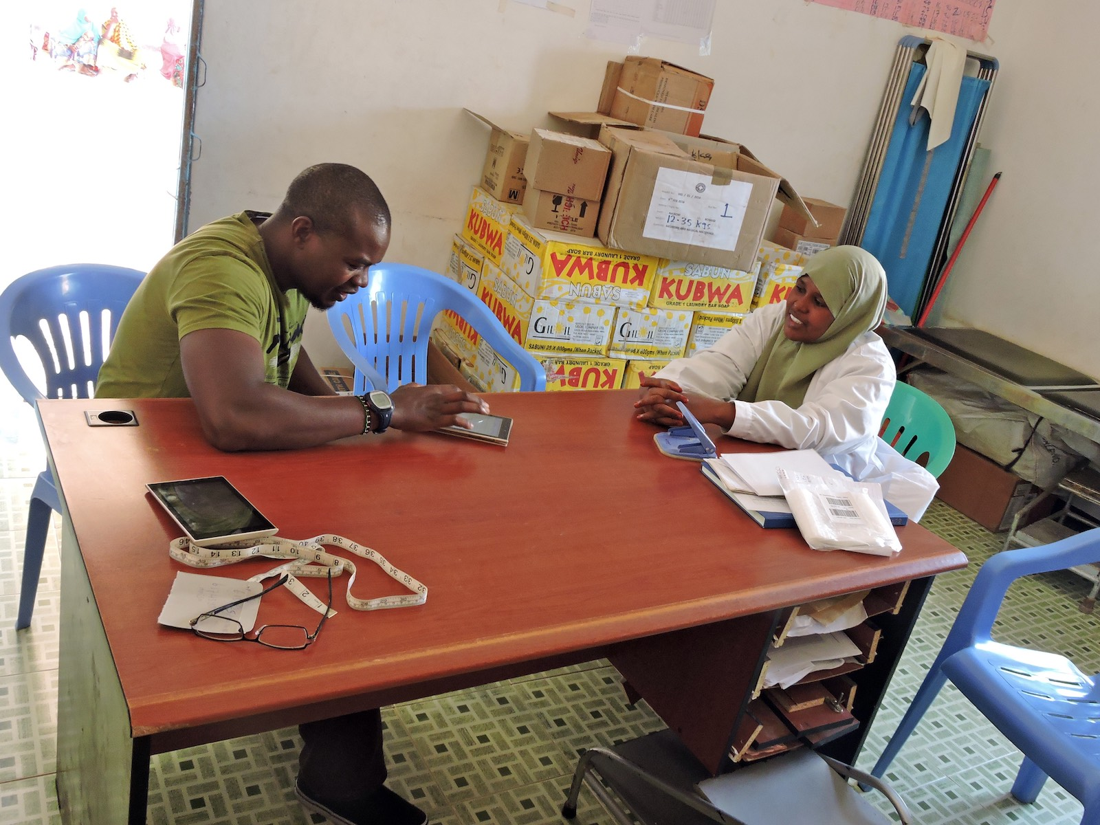 A community health worker conducting an interview and entering research data on a tablet device
