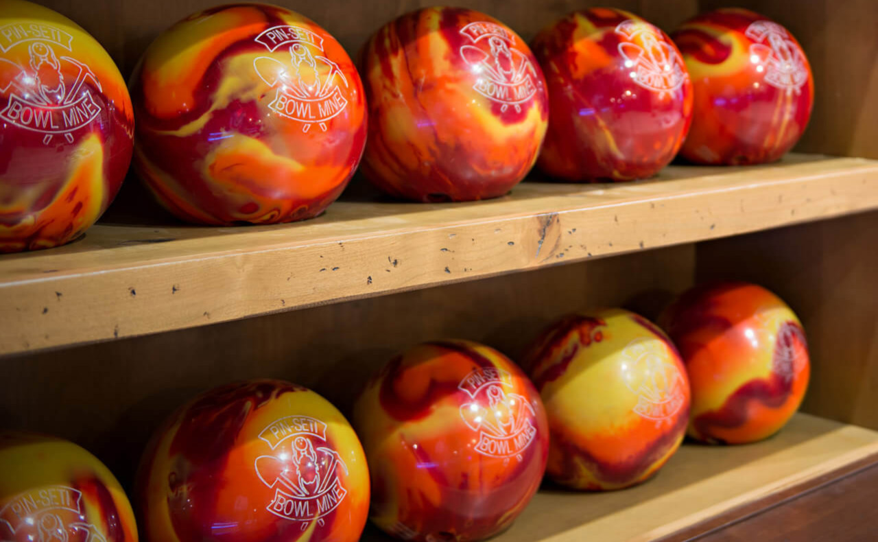 Custom yellow, orange, and red swirl bowling balls on a built-in shelf