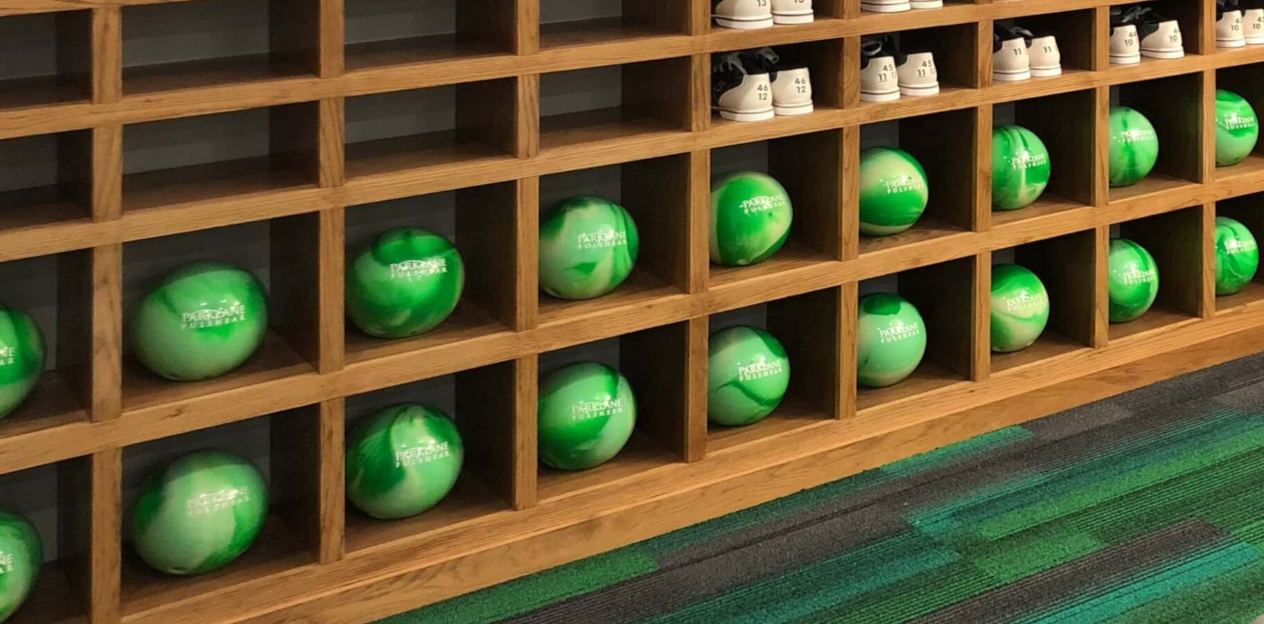 Custom bowling balls in cubbie holes. They are a swirl of light green and dark green.
