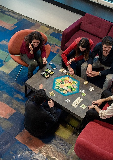 Coworking community members and friends having good fun while playing a board game in one the relaxation common areas in Puzl CowOrKing.