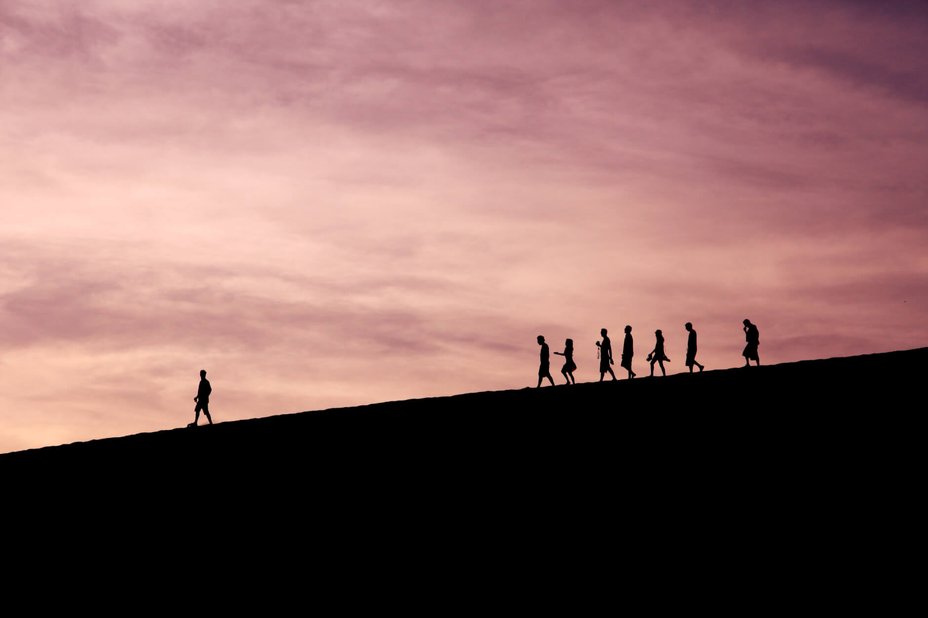 people following a leader down a hill at sunset
