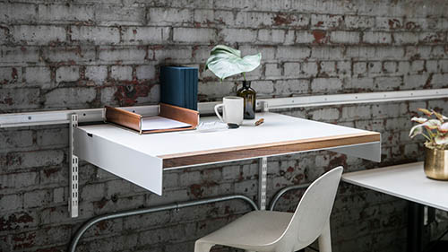 Adjustable desk on wall