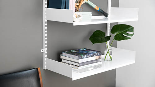 white shelf design with plant vase and plant and tennis racket
