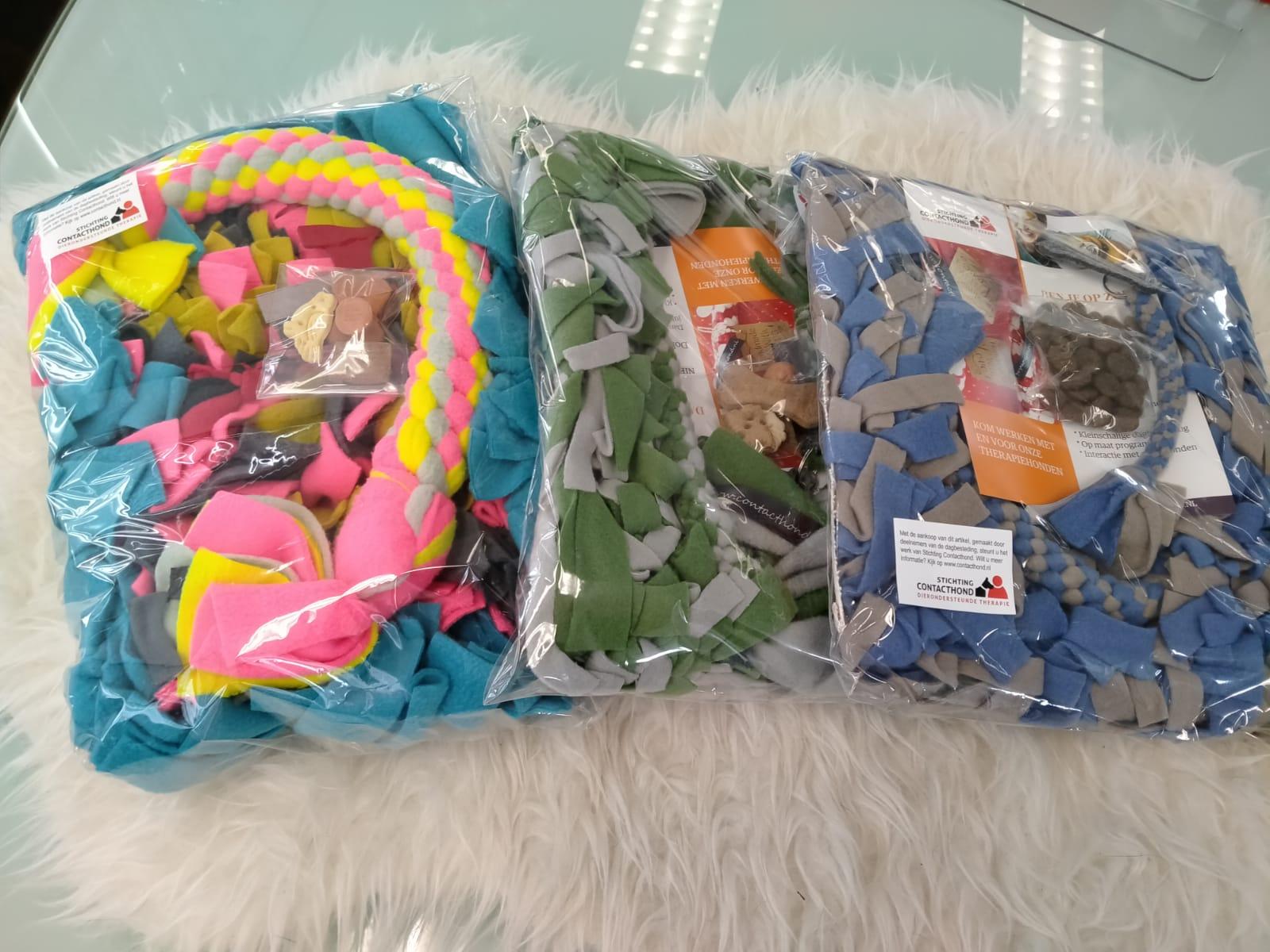 Een pakket bestaat uit een snuffelmat met een grof vezel achterkant (handwas), een sleutelhanger, fleece speeltouw en puzzel flos. De pakketten verschillen in kleur en prijs. Informeer naar de mogelijkheden.