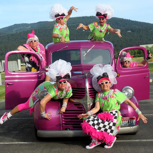 Women posing on pink classic truck