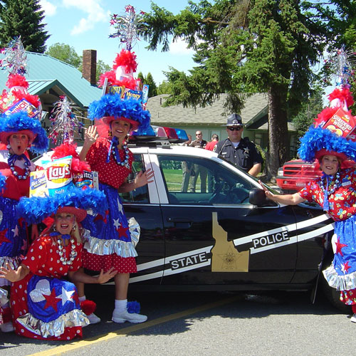 Women in costume posing in front of patrol car